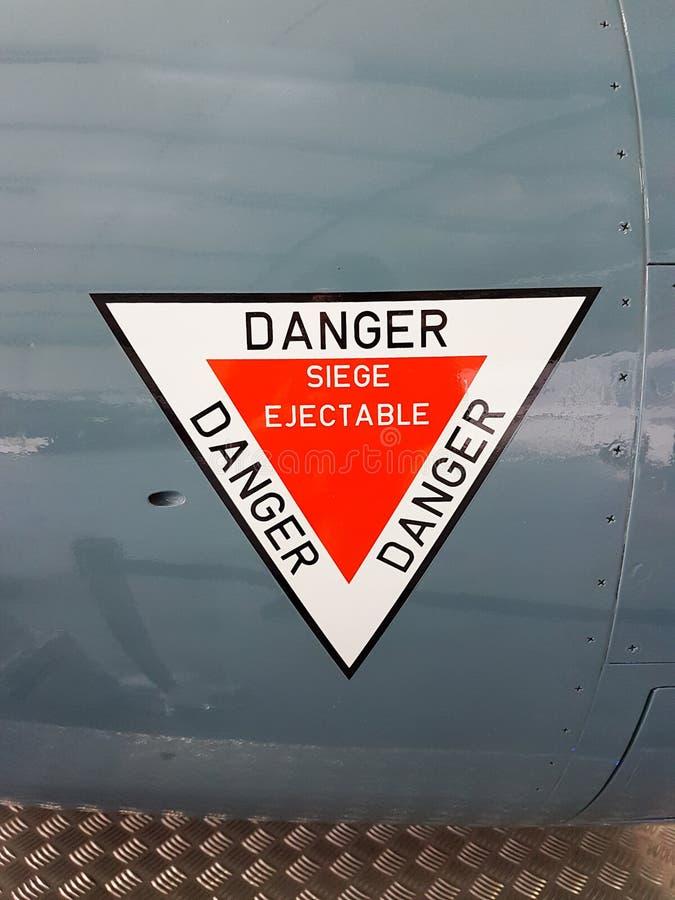 Las etiquetas engomadas firman en el avión escriben en el peligro francés de éjectable del siège significan peligro del asiento fotografía de archivo libre de regalías