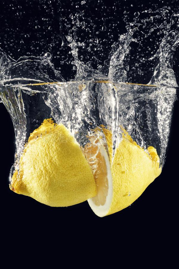 Las explosiones y salpican de un limón lanzado en el agua fotos de archivo
