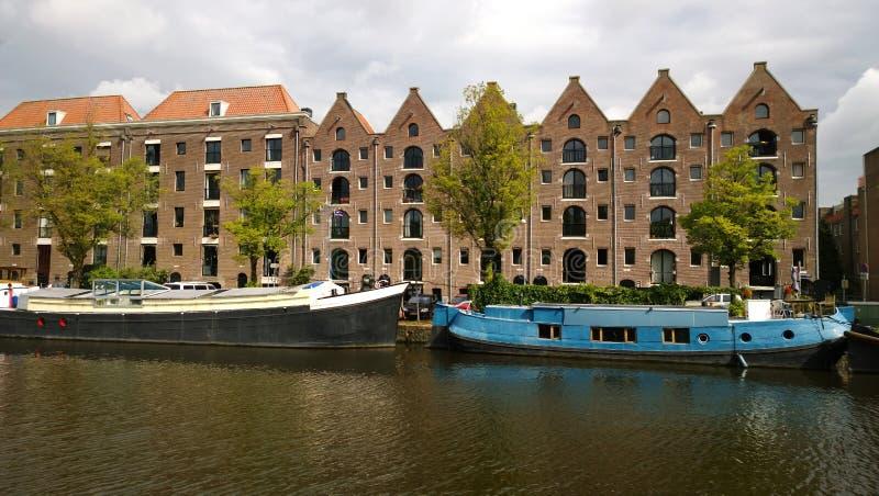 Las fachadas de las casas y de los barcos a lo largo de la costa en Amsterdam imágenes de archivo libres de regalías