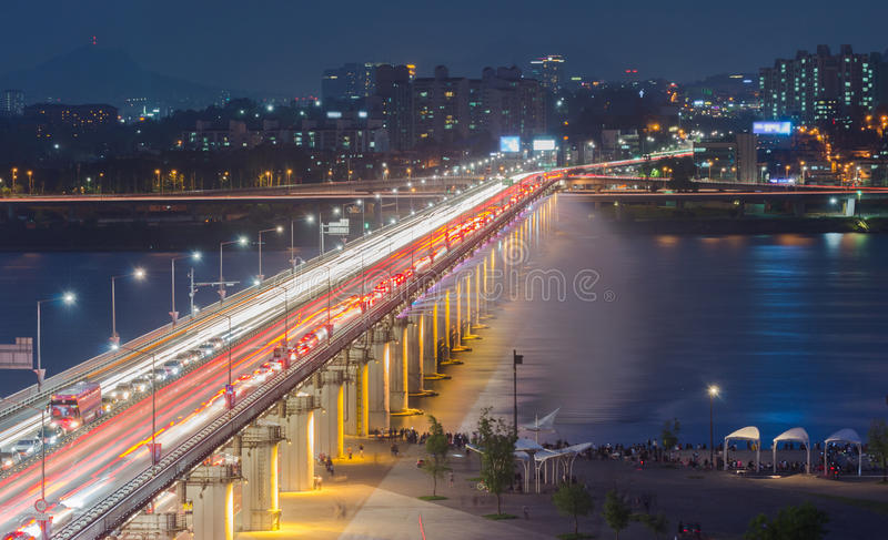 Las faltas de definición del tráfico de la noche más allá de Banpo tienden un puente sobre la fuente del arco iris en Seul, imágenes de archivo libres de regalías