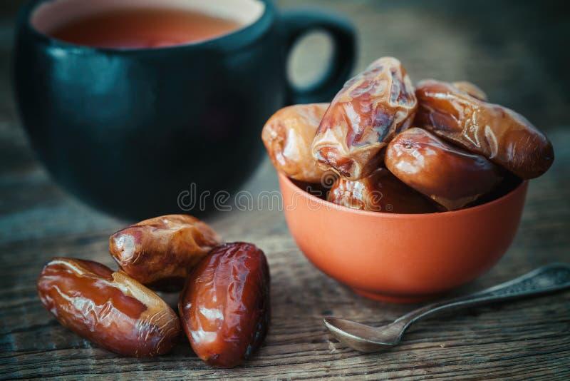 Las fechas dan fruto en cuenco y taza de té en fondo foto de archivo