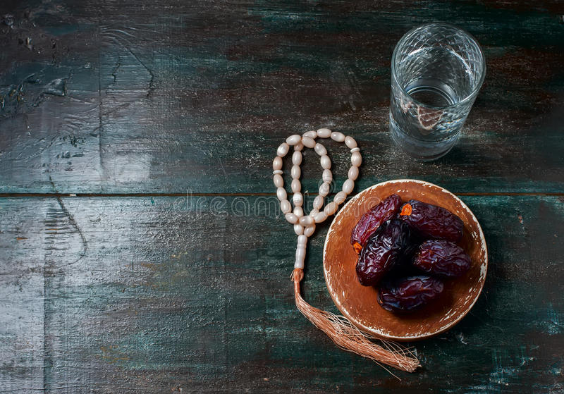 Las fechas todavía dan fruto y la vida del rosario, en un fondo de madera oscuro fotos de archivo
