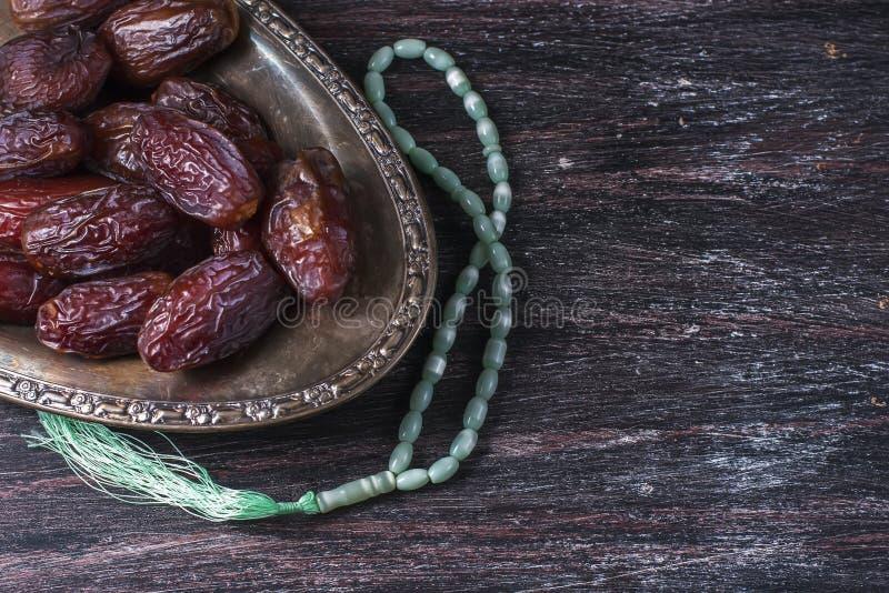 Las fechas todavía dan fruto y la vida del rosario, en un fondo de madera oscuro Concepto de la comida del Ramadán foto de archivo libre de regalías