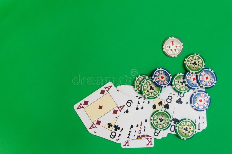 Las fichas de póker apilan y los naipes en la tabla verde imagenes de archivo