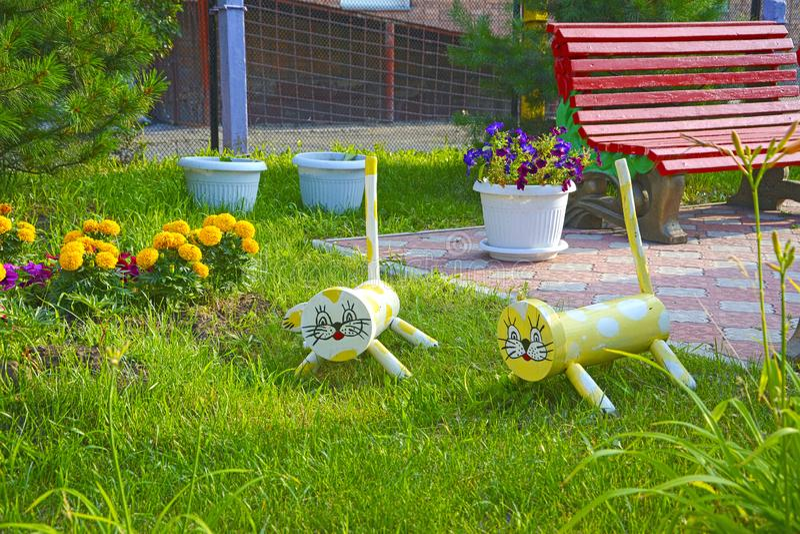 Las figuras de los gatos de los animales de los remanente de la madera y de la basura adornan la cama de flor imagen de archivo