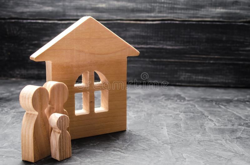 Las figuras de madera de la familia se colocan cerca de una casa de madera El concepto de encontrar un nuevo hogar, moviéndose Un imagenes de archivo