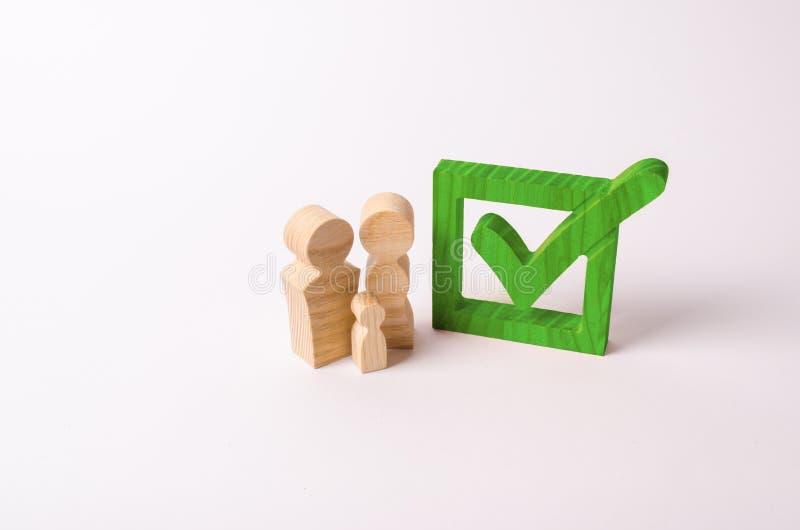 Las figuras de madera de la gente se colocan cerca de la señal verde en la caja Checkbox Voto en elecciones, un referéndum de la  imagenes de archivo