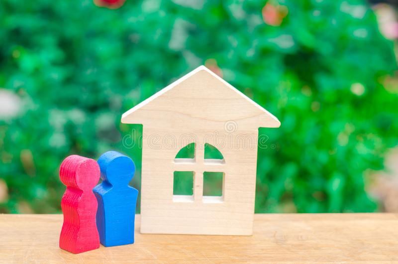 Las figuras de un par joven en amor se están colocando cerca de una casa de madera El concepto de vivienda asequible y barata par imagenes de archivo