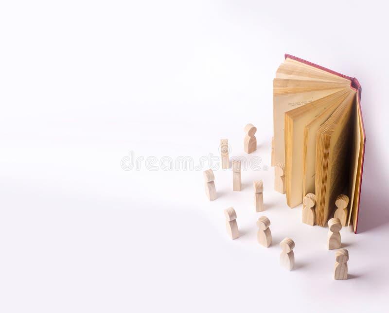 Las figuras miniatura de la gente salen del libro en el real imagen de archivo