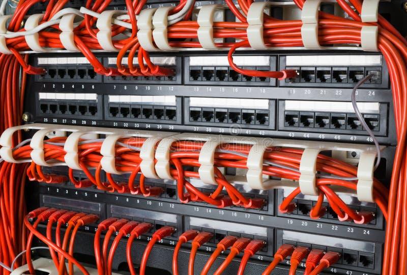 Las filas de los cables de la red conectaron con el eje del router y del interruptor foto de archivo