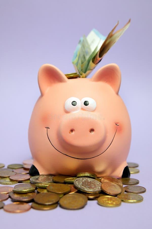 Las finanzas, ahorran el dinero, cuenta, actividades bancarias, hucha rosada sonriente rodeada por las monedas foto de archivo libre de regalías