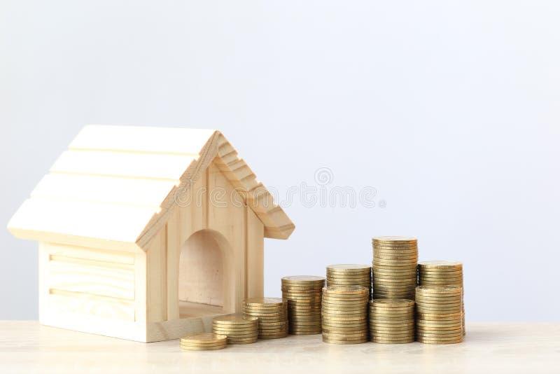 Las finanzas, la pila de dinero de las monedas y la casa modelo en el fondo del wtite, dinero del ahorro para se preparan en conc imagenes de archivo
