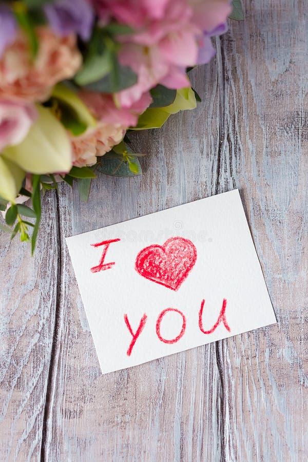 Las flores agrupan en un fondo ligero de madera con la etiqueta Te amo imágenes de archivo libres de regalías