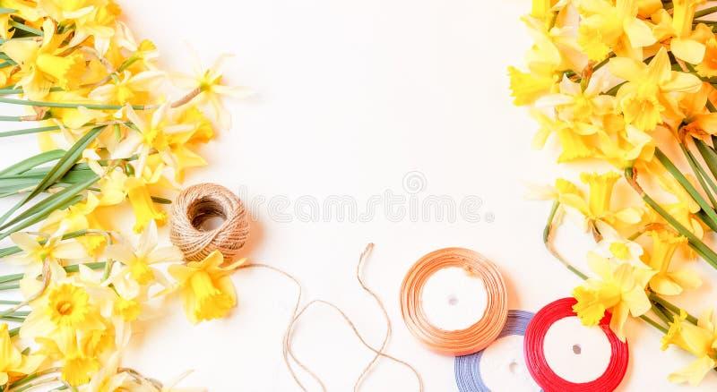 Las flores amarillas son narcisos y cinta coloreada con una longitud de la cuerda en un fondo blanco, visión superior fotos de archivo