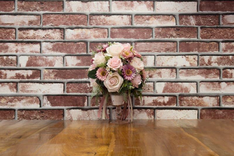 Las flores artificiales pusieron la madera de la terraza con la pared de ladrillo en vintag imagenes de archivo
