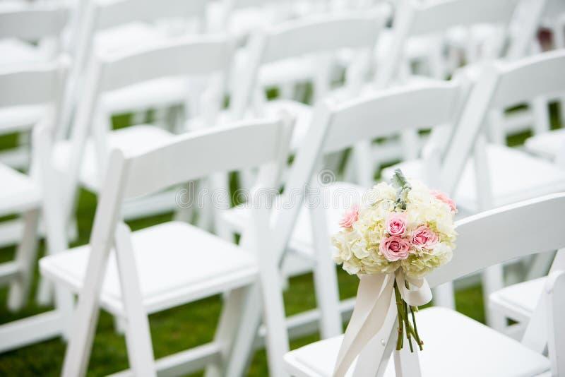 Las flores ataron a los asientos en una ceremonia de boda fotografía de archivo libre de regalías