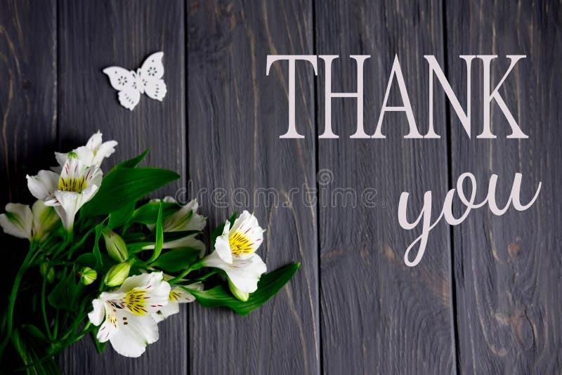 Las flores blancas del Alstroemeria en un fondo de madera oscuro con una inscripción le agradecen Gracias las palabras fotografía de archivo libre de regalías