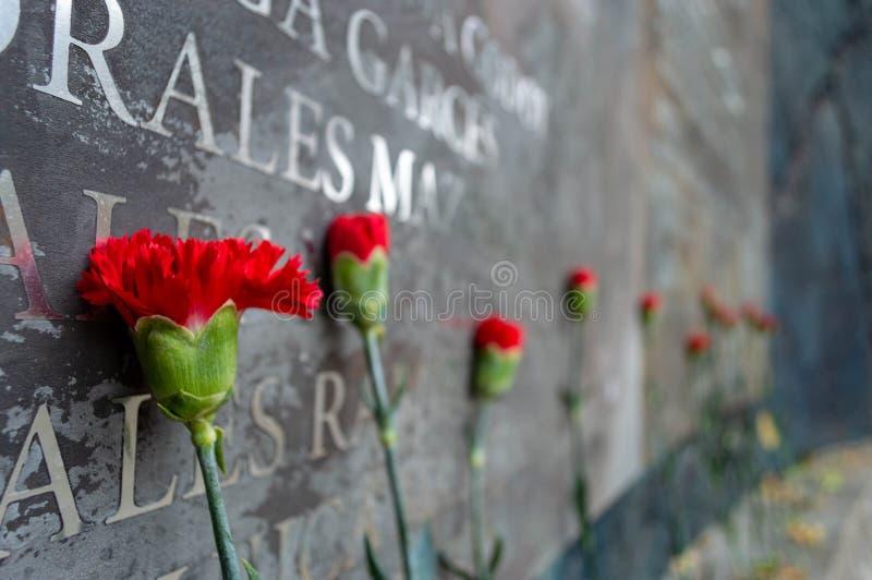 Las flores conmemorativas ponen contra los nombres de las víctimas fotografía de archivo libre de regalías