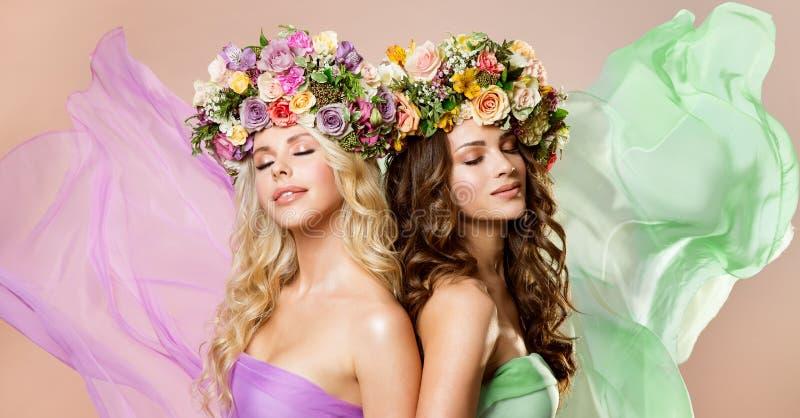 Las flores de los modelos de moda enrruellan el peinado, retrato feliz de la belleza de dos mujeres, Rose Flower en pelo imagen de archivo