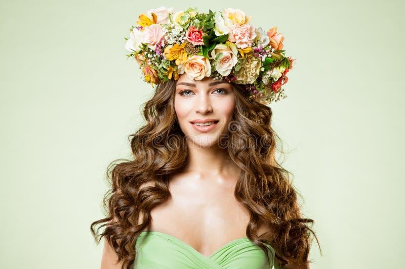 Las flores de los modelos de moda enrruellan el retrato de la belleza, maquillaje de la mujer con Rose Flower en el peinado, much fotografía de archivo libre de regalías
