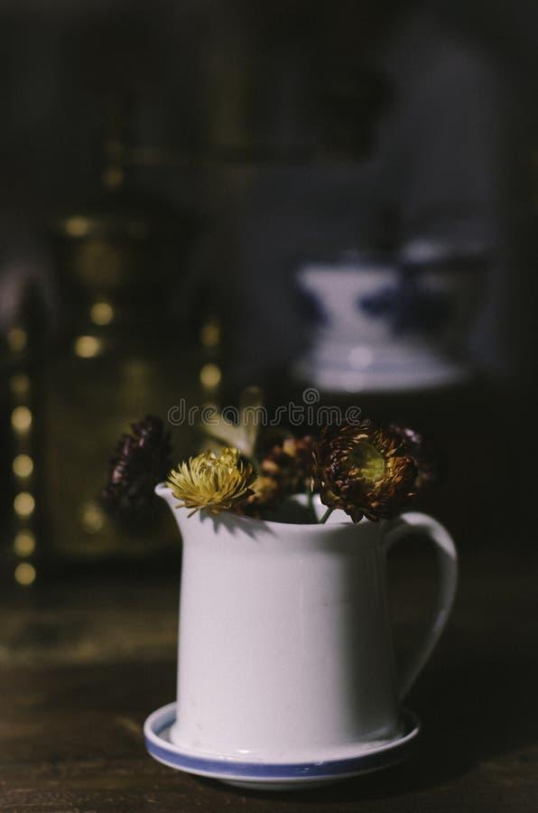 Las flores en el tarro con la ventana calientan la luz foto de archivo