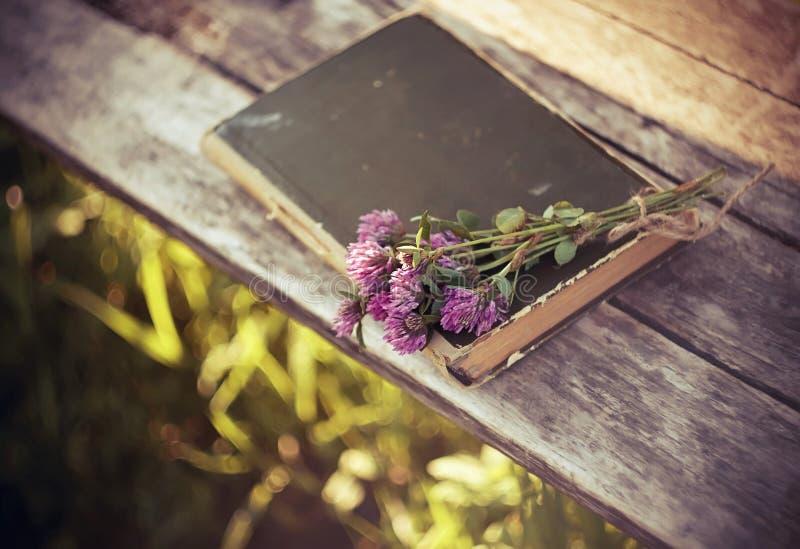 Las flores rosadas del trébol mienten así como el libro cerrado en una tabla de madera fotografía de archivo libre de regalías