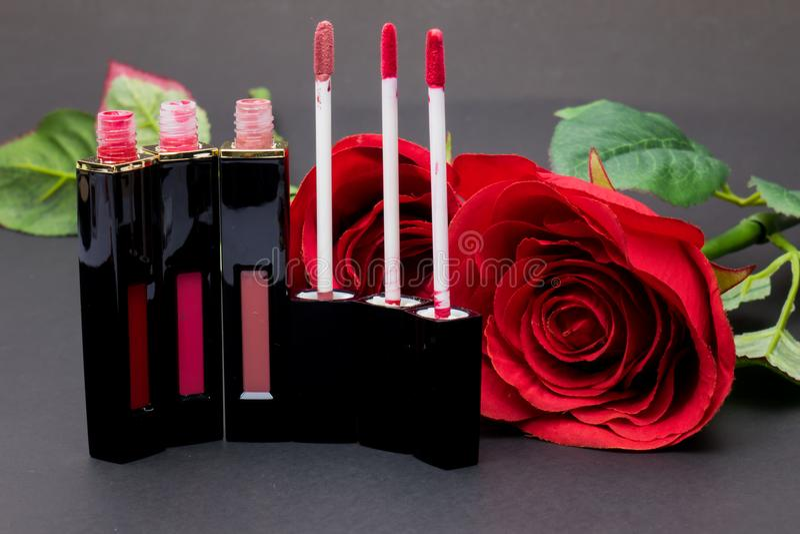 Las flores subieron, los labios de las aplicaciones del cepillo del polvo y del lápiz labial en backg negro foto de archivo