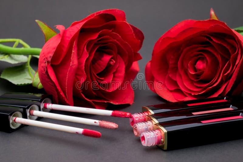 Las flores subieron, los labios de las aplicaciones del cepillo del polvo y del lápiz labial en backg negro fotografía de archivo