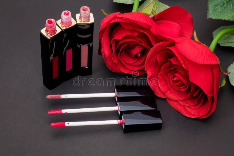 Las flores subieron, los labios de las aplicaciones del cepillo del polvo y del lápiz labial en backg negro imagen de archivo