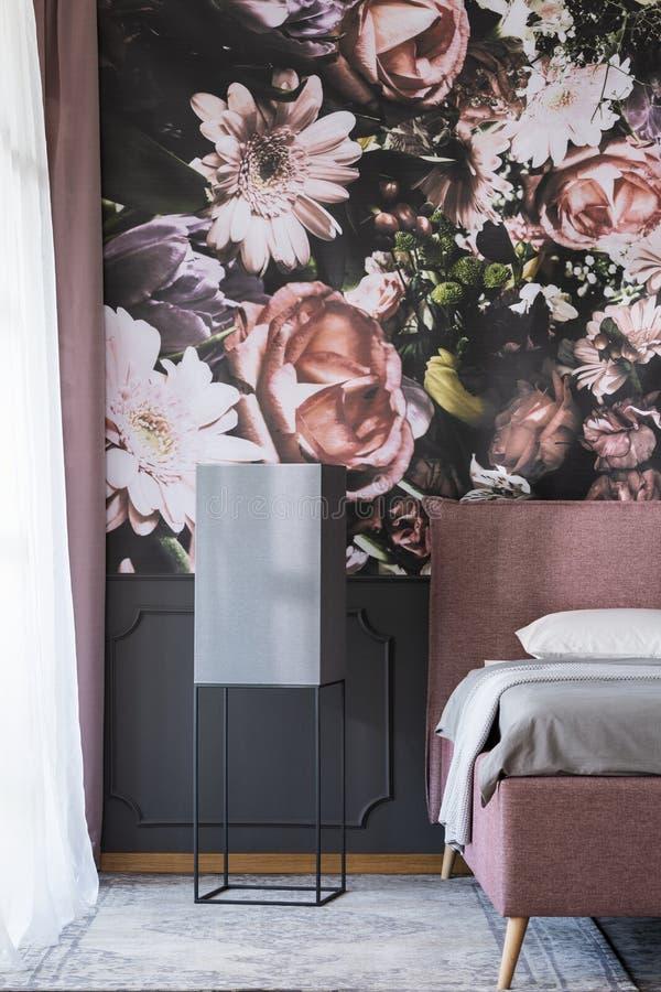 Las flores wallpaper en interior oscuro del dormitorio con la tabla negra siguiente imagenes de archivo