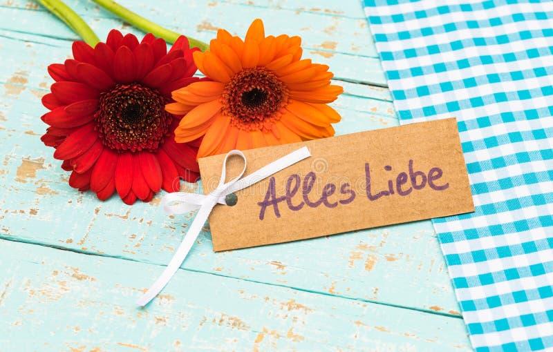 Las flores y la tarjeta con el texto alemán, Alles Liebe, medios aman para el día de los padres o de madres imagen de archivo libre de regalías