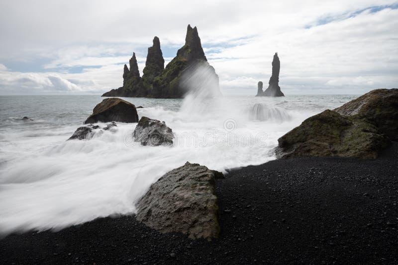 Las formaciones de roca del basalto pescan los dedos del pie con cebo de cuchara en la playa negra Reynisdrangar, Vik, Islandia imágenes de archivo libres de regalías