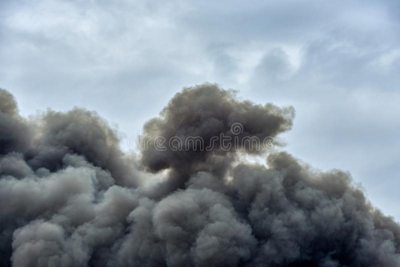 Las formas y las formas en una nube de la contaminación tóxica fuman de un fuego de la fábrica contra un cielo azul limpio imagen de archivo