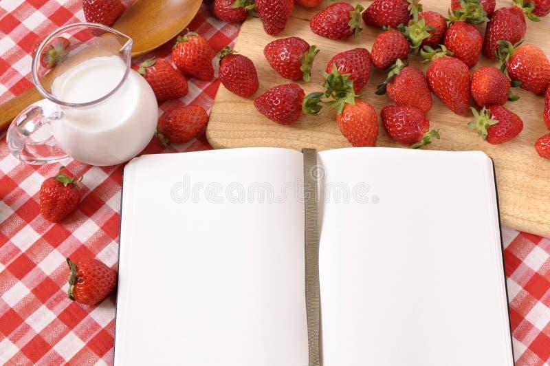 Las fresas baten el fondo, libro de la receta, espacio de la copia imagen de archivo