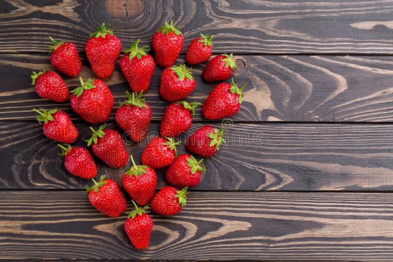 Las fresas frescas ponen en orden forma del corazón en viejo fondo de madera fotografía de archivo libre de regalías