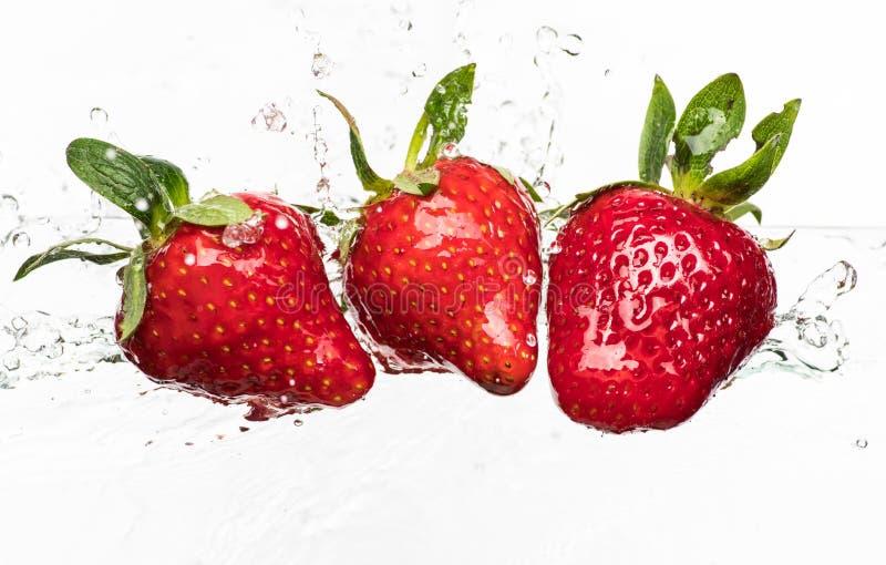 Las fresas rojas maduras se lanzan y se caen en el agua chispeante, muchas burbujas foto de archivo libre de regalías