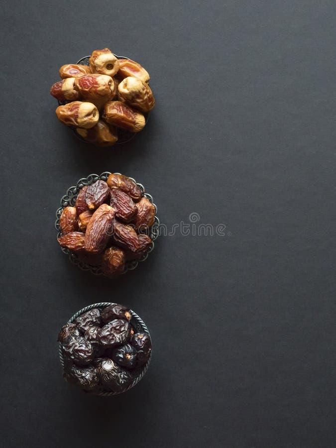 Las frutas de las fechas del saudí se presentan en una tabla oscura foto de archivo