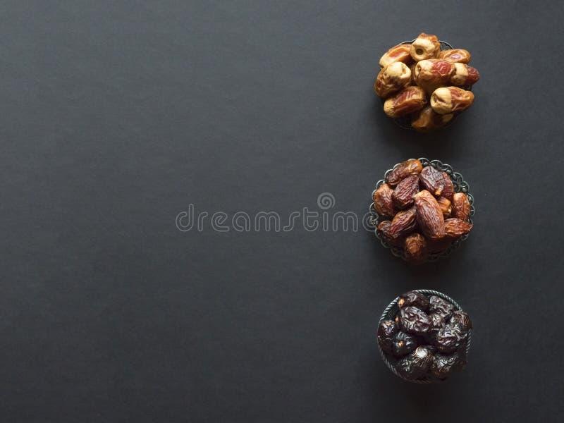 Las frutas de las fechas del saudí se presentan en una tabla oscura fotografía de archivo
