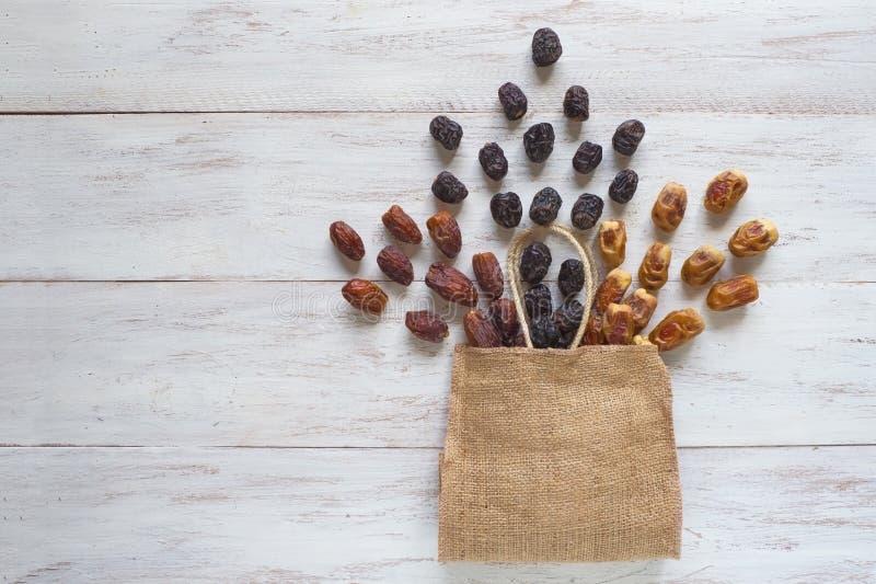 Las frutas de las fechas se presentan en una tabla de madera con un bolso imágenes de archivo libres de regalías