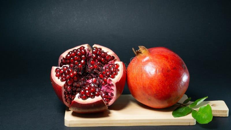 Las frutas de la granada están en el tablero de la cocina que se abre un pie y las semillas son visibles cerca del segundas imagen de archivo libre de regalías