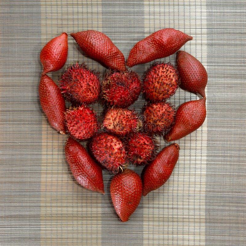 Las frutas del Rambutan y del dragón organizadas en corazón forman en fondo de bambú marrón de la estera fotos de archivo libres de regalías