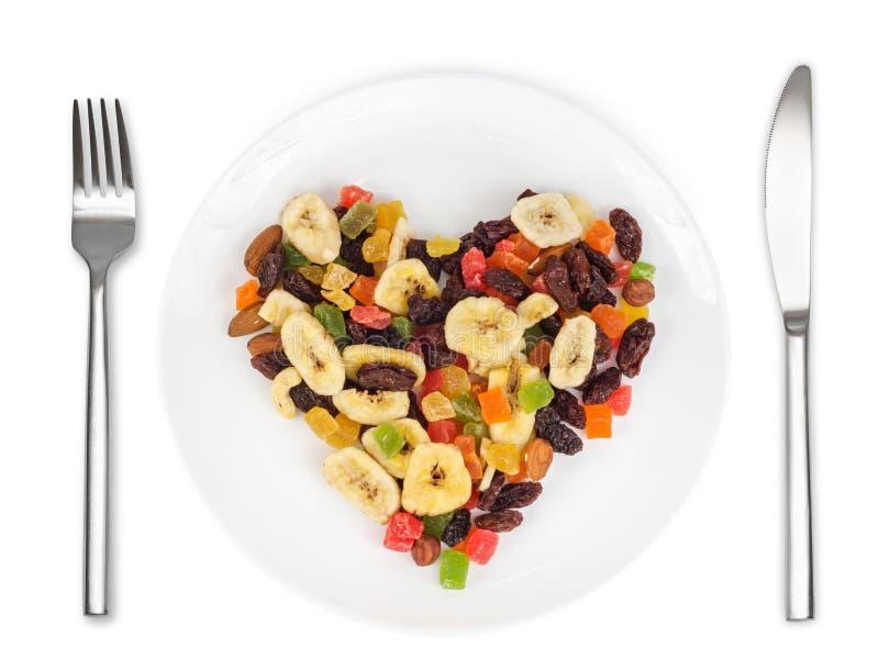 Las frutas secadas en corazón forman en la placa blanca fotografía de archivo