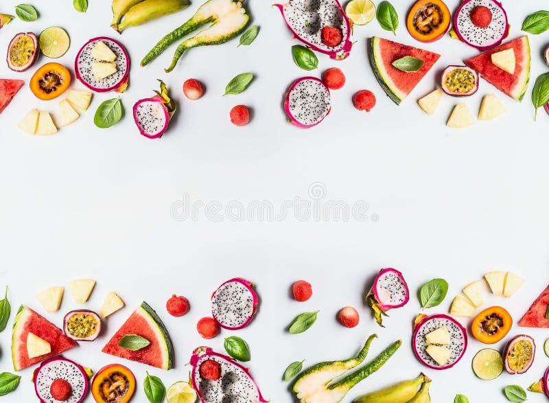 Las frutas tropicales del diverso verano cortan el marco en el fondo blanco, visión superior, disposición plana imagen de archivo libre de regalías