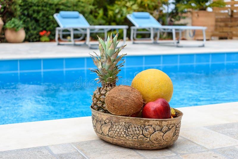 Las frutas tropicales mienten en una cesta en el fondo de la piscina azul imagen de archivo