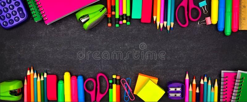 Las fuentes de escuela doblan la bandera de la frontera, opinión superior sobre un fondo de la pizarra con el espacio de la copia imágenes de archivo libres de regalías