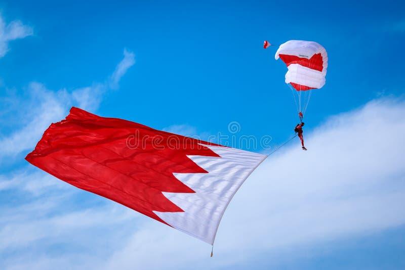 Las fuerzas especiales de la defensa de Baharin se lanzan en paracaídas equipo de la exhibición en Bahrein Airshow internacional, imagen de archivo libre de regalías