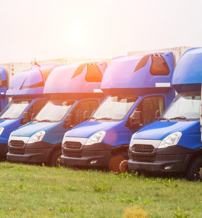 Las furgonetas azules del cargo se colocan en fila, trueque y logística, transporte por camión y sol imagenes de archivo