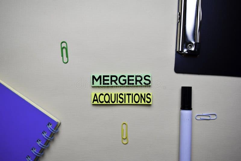 Las fusiones y las adquisiciones mandan un SMS en notas pegajosas con el escritorio de oficina Concepto del intercambio del merca foto de archivo