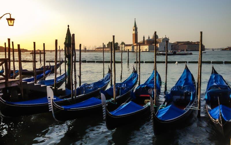 Las góndolas ancladas en el embarcadero de San Marco ajustan en la salida del sol en Grand Canal hacia San Giorgio Maggiore, Vene imagenes de archivo