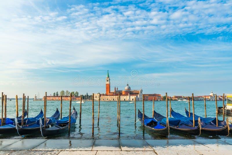 Las g?ndolas amarraron por la Plaza de San Marcos con la iglesia de San Giorgio di Maggiore en el fondo Venecia, Venezia, Italia imagenes de archivo